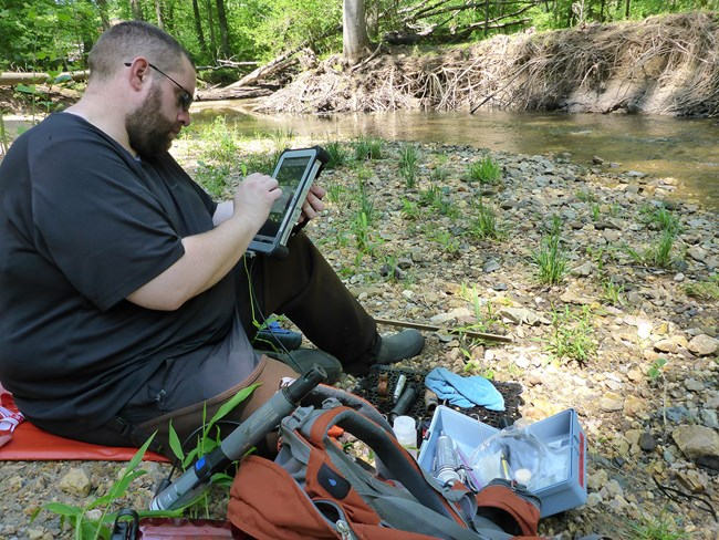 A man sits near a stream to enter data into a tablet computer.