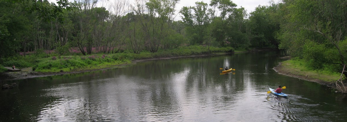 Two paddlers make their way down the Concord River.