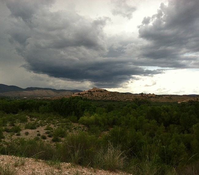 Dark clouds gather over a desert butte.