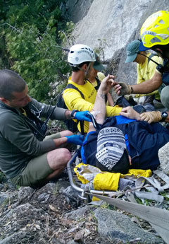 Hiking lying in litter with rescuers providing care