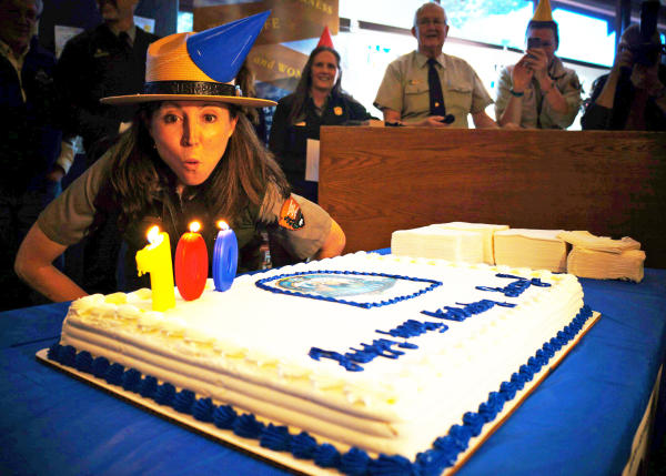 A uniformed female park ranger blows out the candles on Rocky's 100th birthday cake