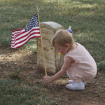 Small child placing a flag in front of a Civil War headstone in the National Cemetery
