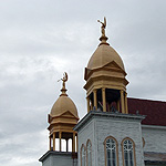 Gold domes of ornate church with angel statues on top