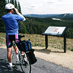 A bicyclist takes in the view from atop Mt. Washburn