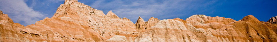 Badlands formations against the blue sky; photo by Rikk Flohr