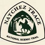 logo of the natchez trace national scenic trail with a man on a horse in a triangular shaped logo