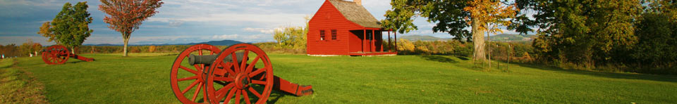 Scenic rural landscape with green lawn, cloud-flecked blue sky, and autumn foliage punctuated by a small, deep red farmhouse and red cannon carriages.