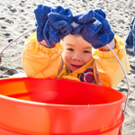 Child with a bucket, helping to clean up Ocean Beach at the California Coastal Cleanup Day.