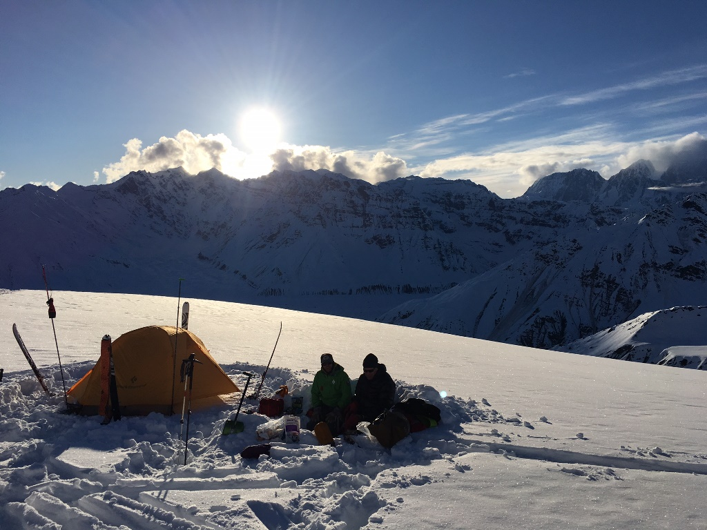 Two climbers sit outside a tent on a snowfield overlooking distant mountain peaks