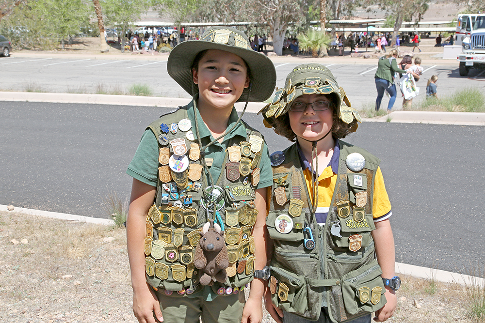 two junior rangers with a lot of badges