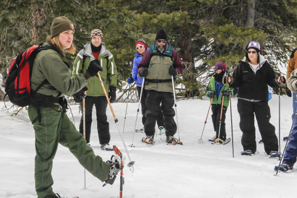 A ranger and visitors lift up their snowshoe-shod feet while standing on snow