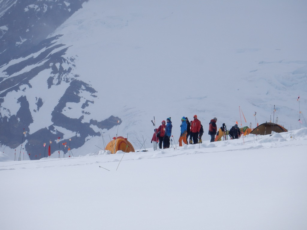 Brightly clothed climbers watch aircraft land at the Kahiltna Glacier