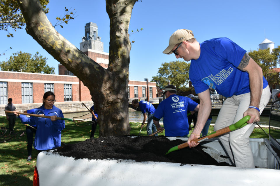 Volunteers spreading mulch from the back of a pickup truck on Ellis Island