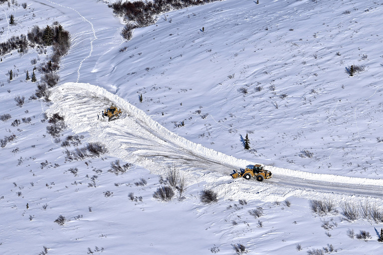 two yellow machines pushing snow around in a frozen landscape, revealing a dirt road