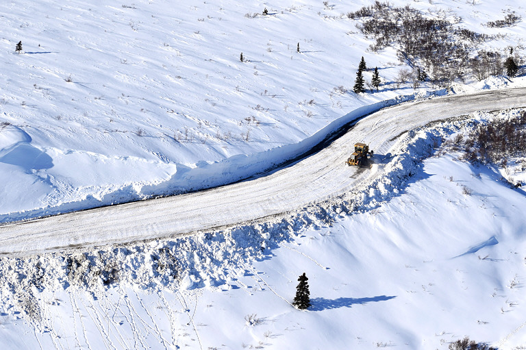 aerial view of a plow driving down a snowy road in a snowy landscape