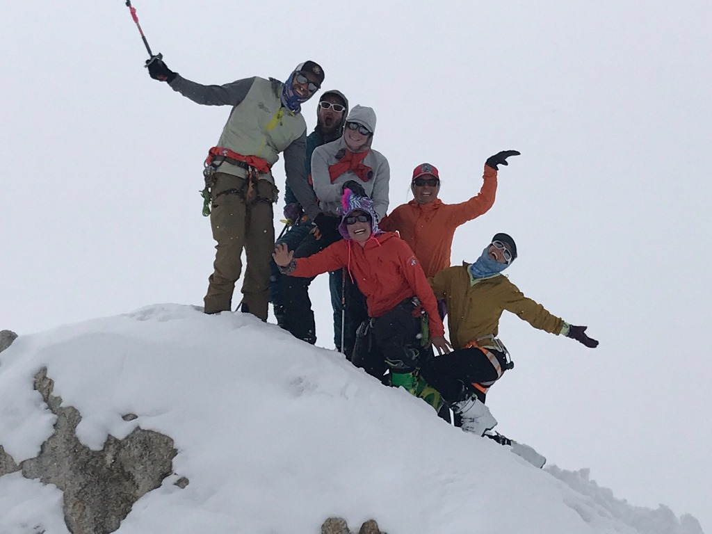 Six patrol members pose on a snowy rock outcropping