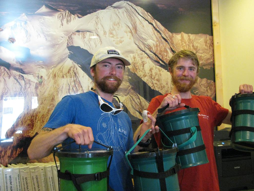 Two climbers holding Clean Mountain Cans