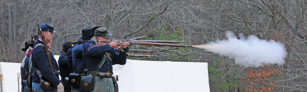 Union reenactors firing muskets at Fort Donelson