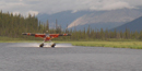 A float plane landing on a lake in the park.
