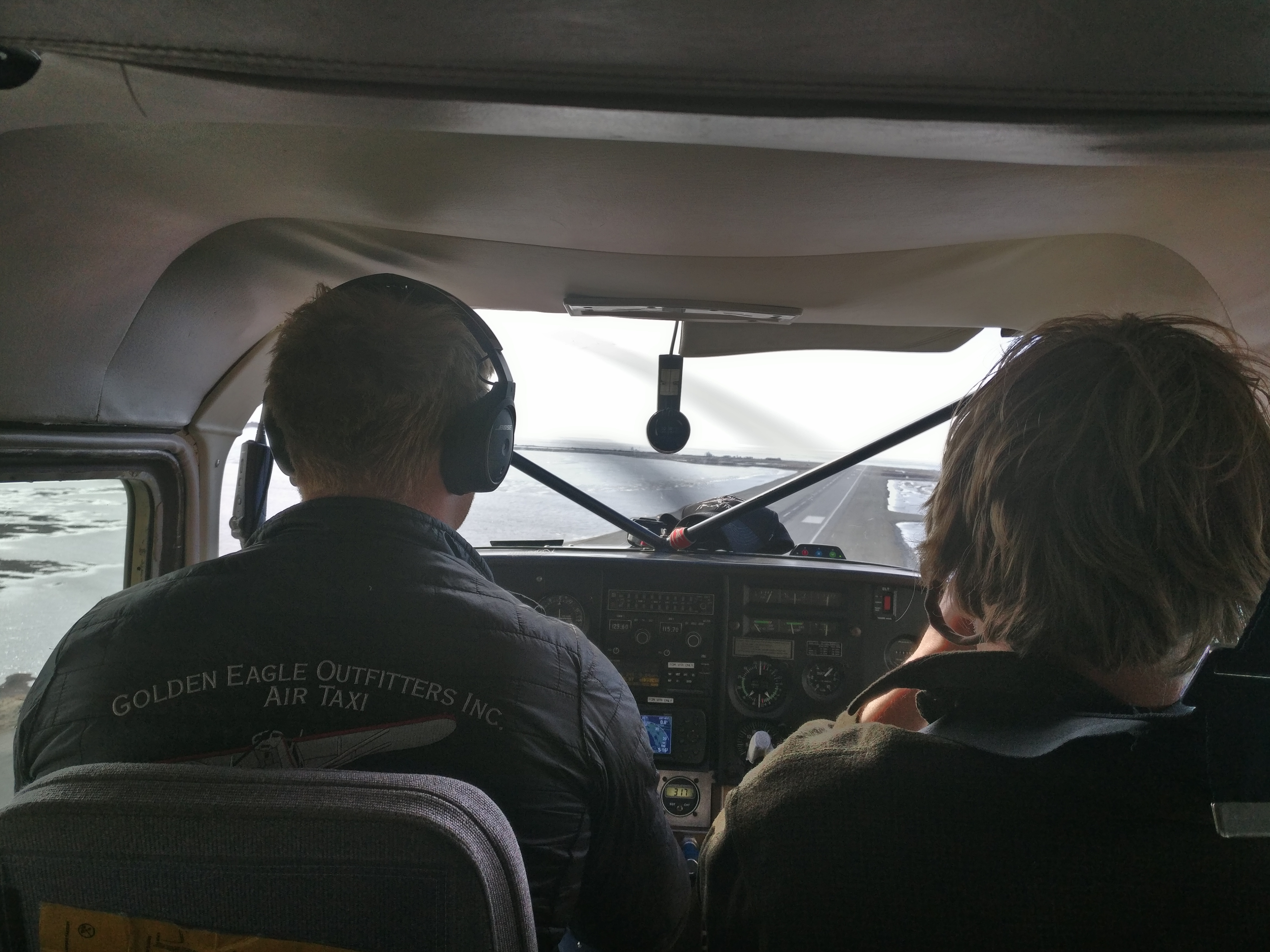 A pilot and passenger in a small plane make their final approach to the runway of the airport in Kotzebue.