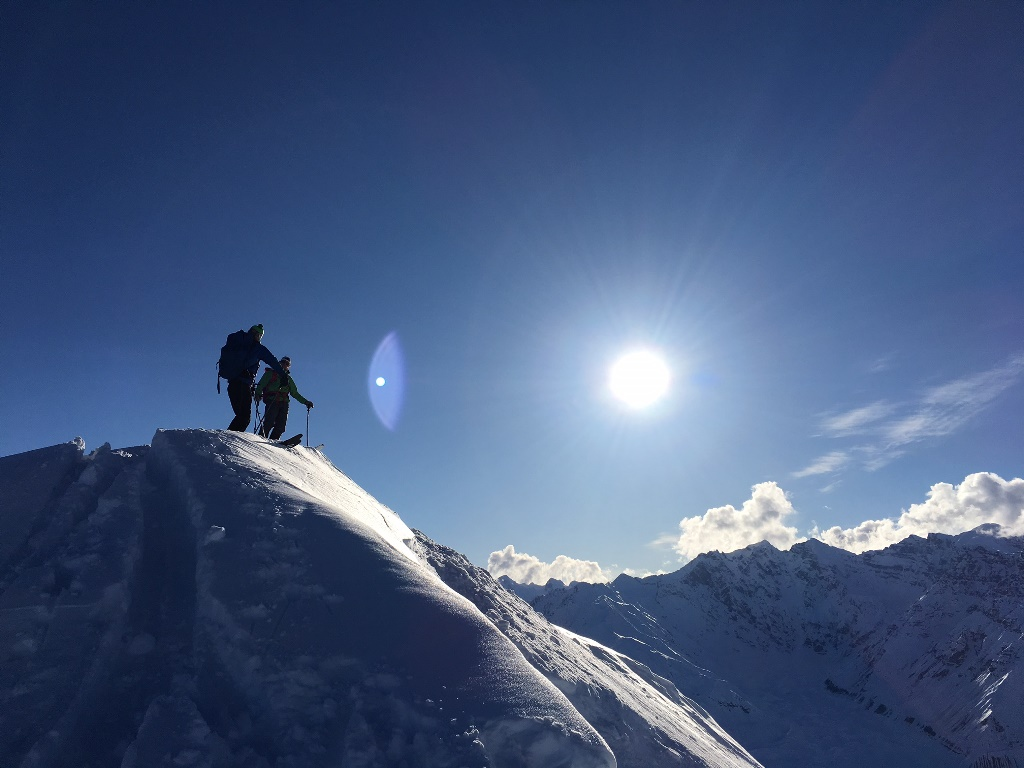 Two skiers in silhouette on top of a ridgeline