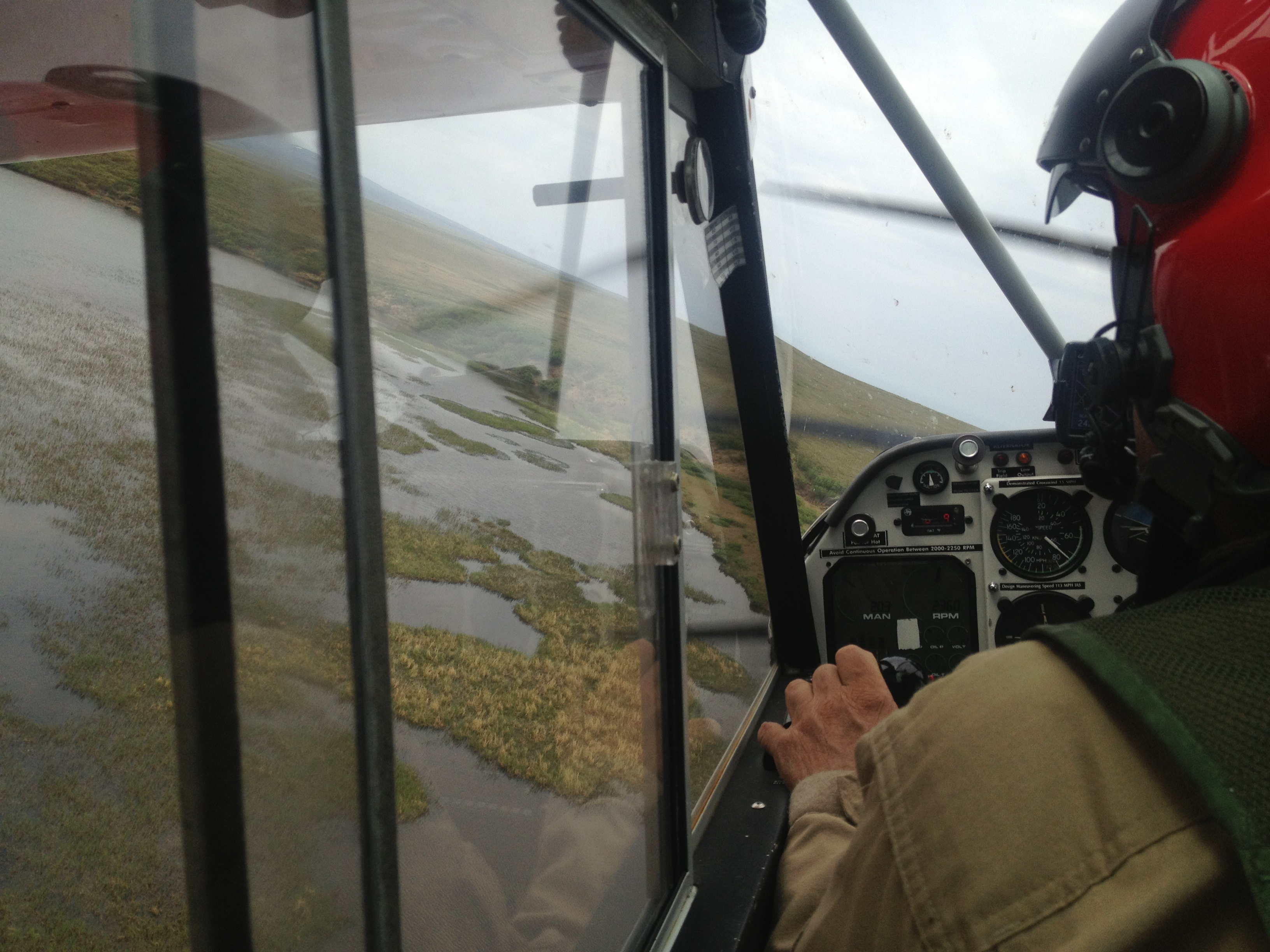 A view from the cockpit of a small plane as the pilot swerves his aircraft in search of loons nesting in marshes in Bering Land Bridge National Preserve.