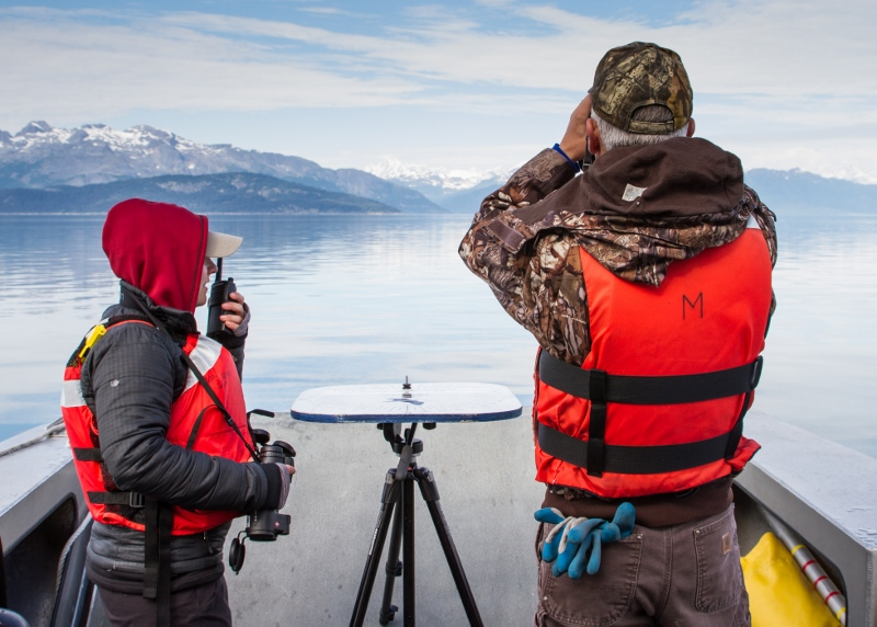Researchers on a boat using binoculars