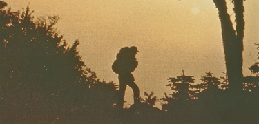 A sunset silhouette of a backpacker on a ridge.