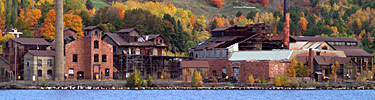 Autumn leaves provide a backdrop for the Quincy Smelting Works located along Portage Lake across from Houghton, Michigan.