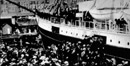 historic photo of a steamship surrounded by a crowd at the docks in Seattle