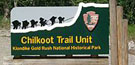 Chilkoot trailhead sign showing the National Park Service arrowhead logo and an outline of people with loads climbing up a steep, snowy pass
