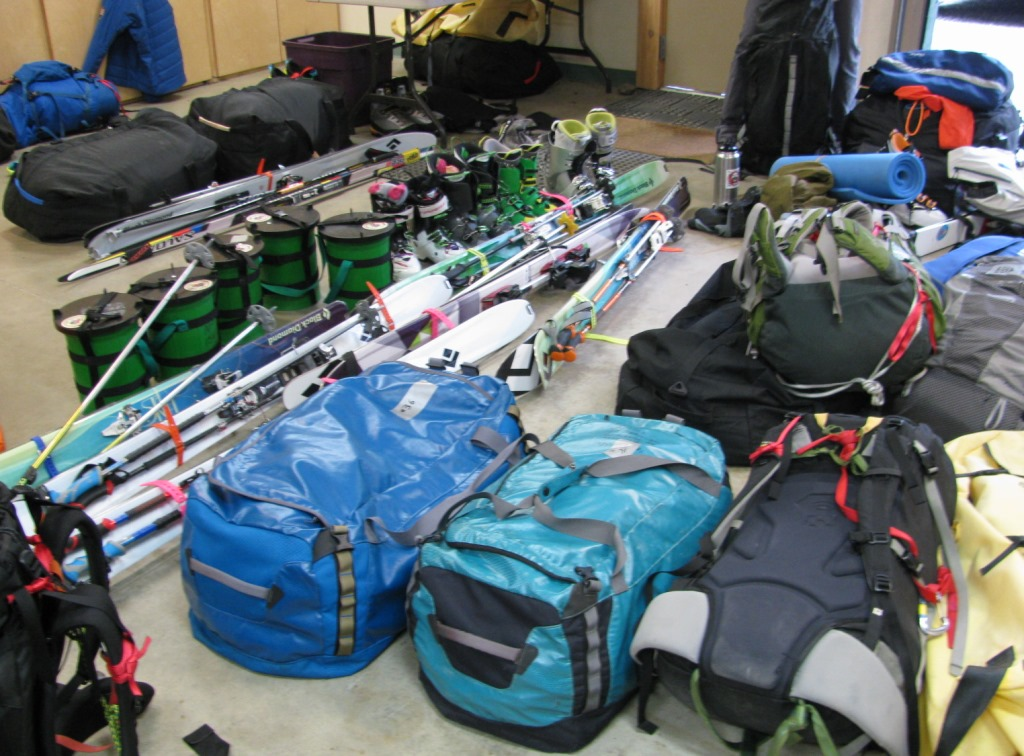 a pile of mountaineering gear, including duffels, skis, backpacks, CMCs and other gear
