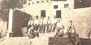 In this sepia-toned photo from 1927, nine men sit and kneel amongst the ruins of a Native American dwelling at Mesa Verde. NPS Photo.