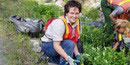 A female volunteer works with park staff on revegetation project