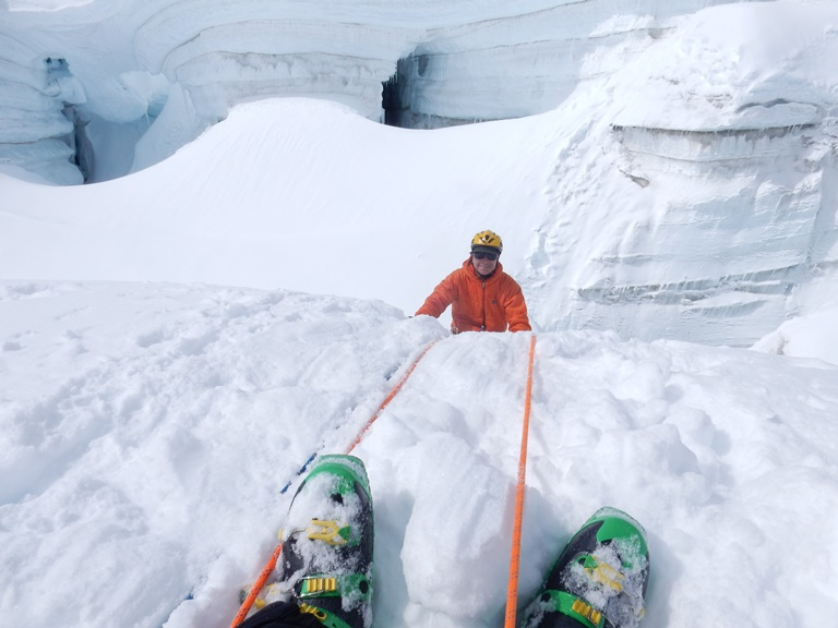 A climber smiles as he climbs out of a crevasse