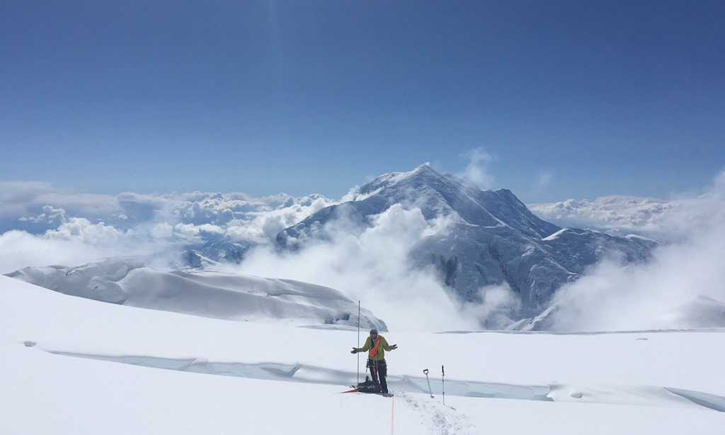A confused climber stands in front of a crevasse, Mount Foraker in the backdrop