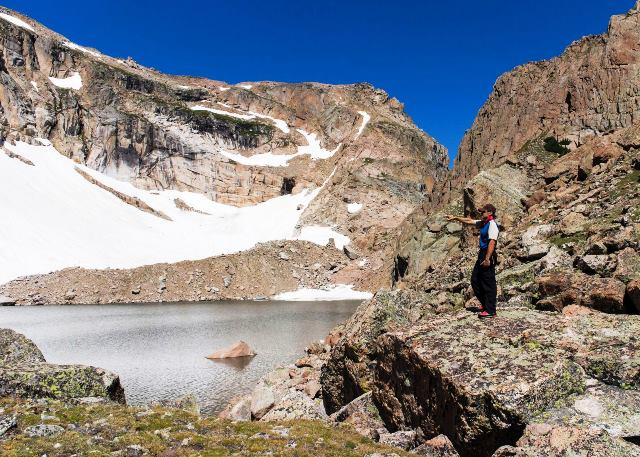 Man standing on rock beside mountain lake pointing to snowfield.