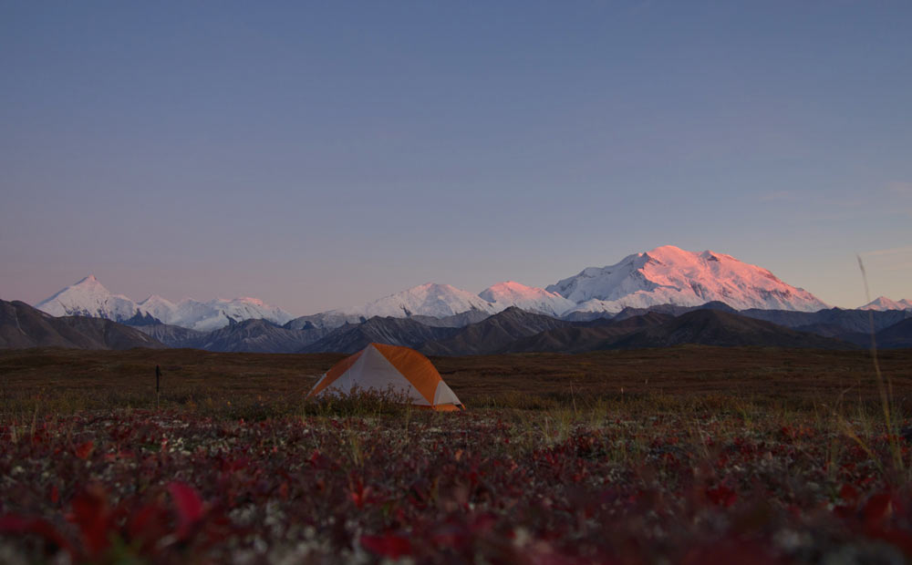 a tent set up in an open field with a view of distant mountains, including one massive mountain tinged pink by the setting sun