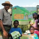 A ranger poses with children near a sign