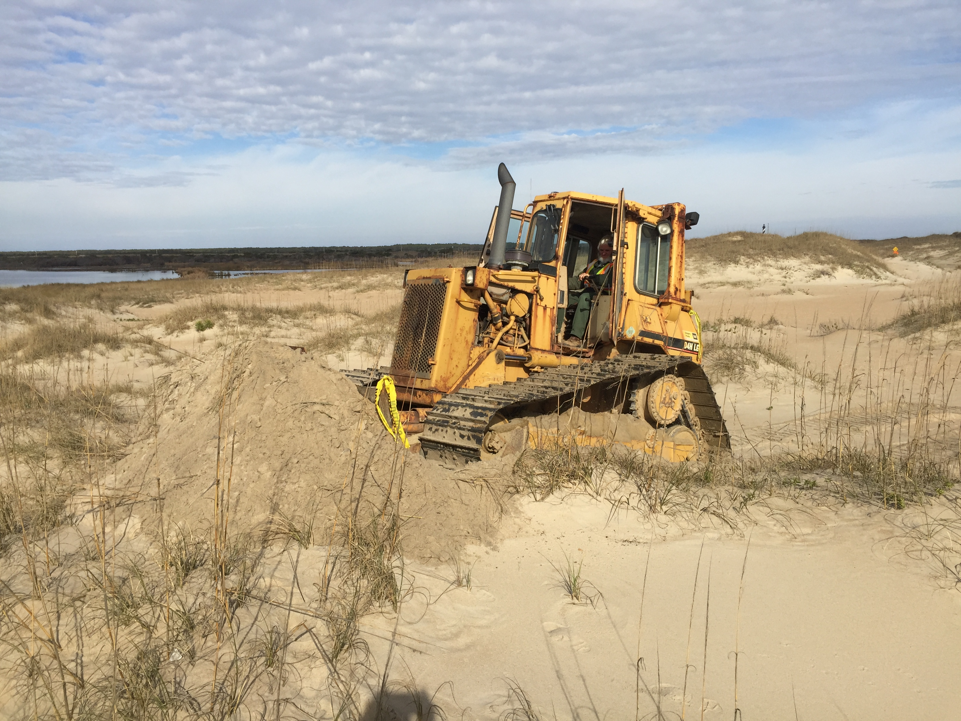 Heavy equipment operator beginning work on Cape Point bypass. Cape Hatteras Lighthouse in background.