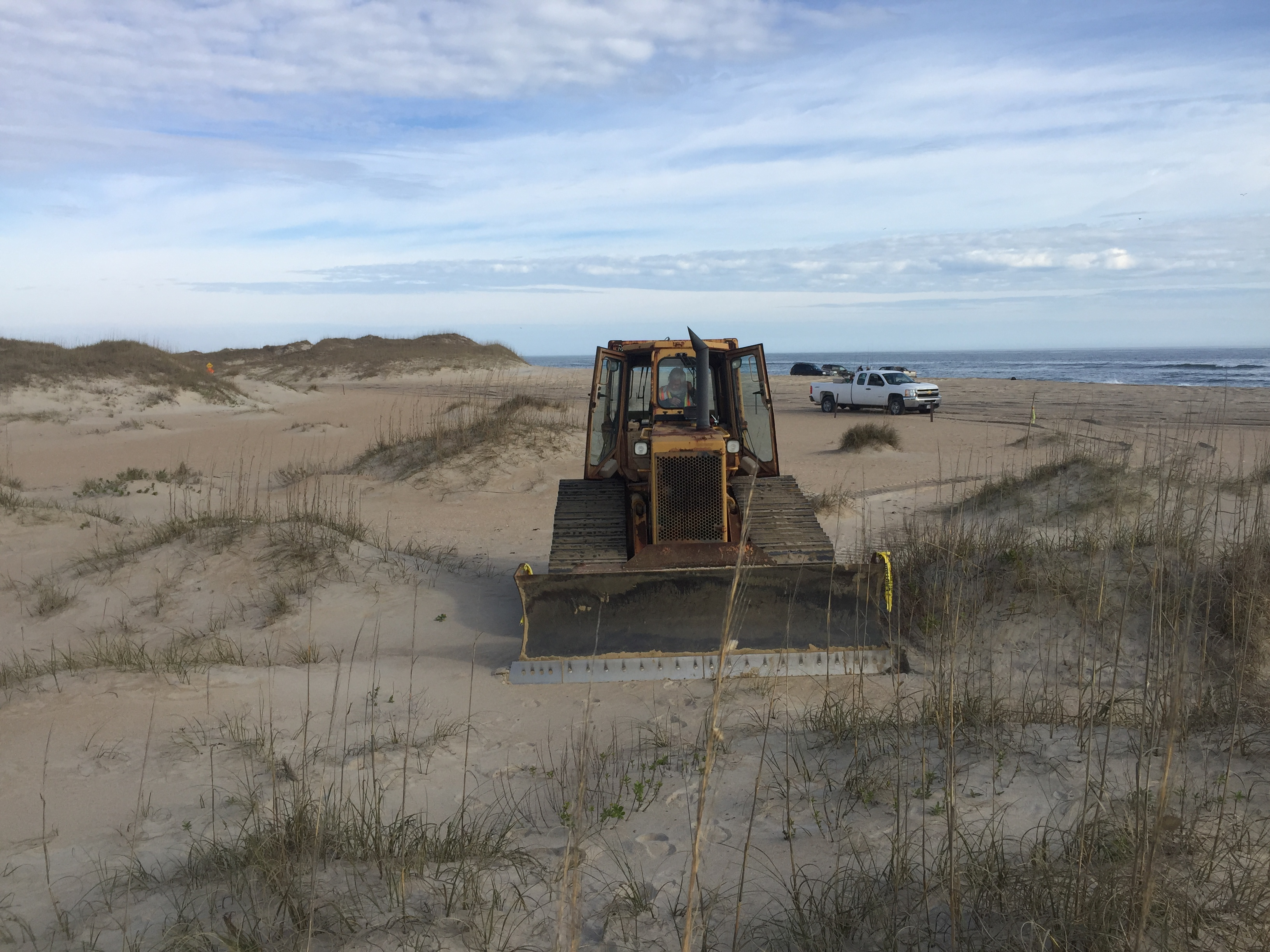 Bulldozer beginning work on Cape Point bypass extension. Park Ranger vehicle and Atlantic Ocean in background.