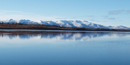 Image of round, snow-capped mountains are reflected perfectly in the calm blue waters of the Kobuk River.