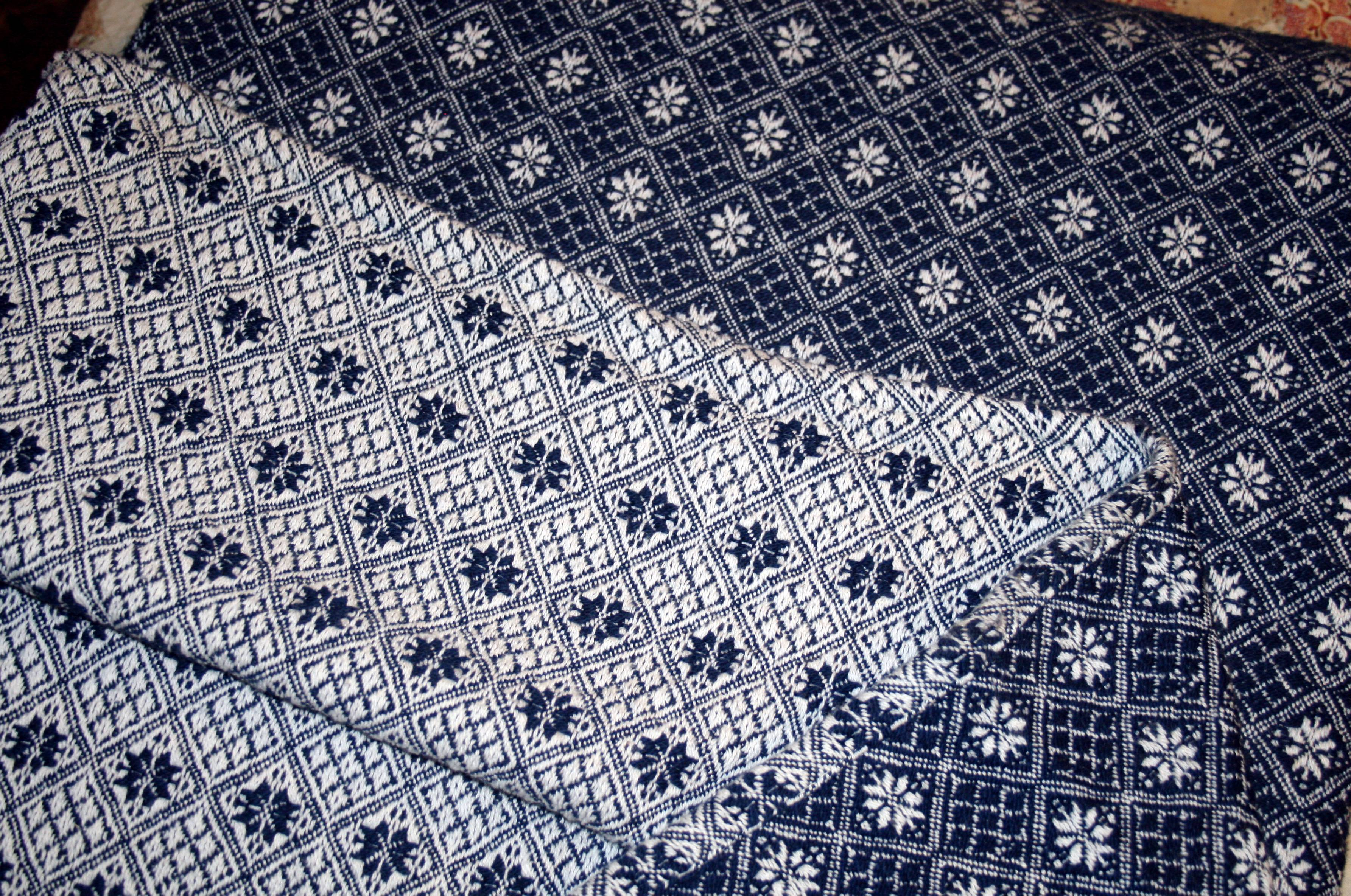 a woven coverlet in navy and white