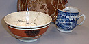 A redware plate with a yellow design, a blue and white Chinese teacup, and a brown and white bowl were found in pieces