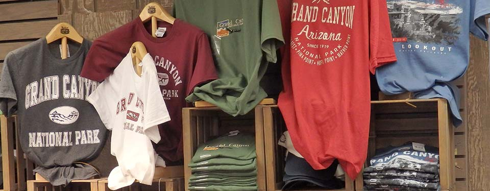A number of colorful t-shirts hanging above a shelf that has folded stacks of the shirts on display.