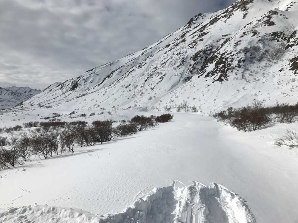a snow covered mountain with a snow-covered road along its flank