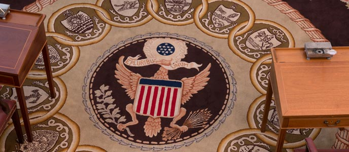Color photo of a detail from the carpet in the Senate Chamber focusing on the Great Seal in the center surrounded by smaller interlocking circles containing coats of arms for the original states.