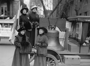 Historic black and white photo of a replica of the Liberty Bell on the back of a truck, surrounded by women dressed in long dresses and hats.