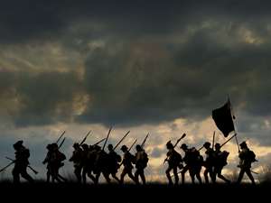 soldiers in silhouette with dark clouds behind