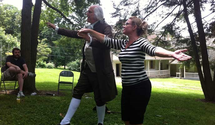 A teacher dances with a man portraying George Washington.